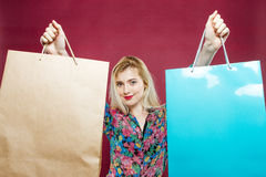 Beautiful Woman with Long Hair is Enjoying Shopping. Portrait of Amazing Blonde with Two Paper Bags in Colorful Shirt on Stock Images