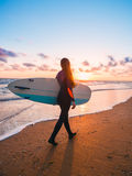 Beautiful woman with long hair go to surfing. Surfgirl with surfboard on a beach at sunset or sunrise. Surfer and ocean Stock Photos