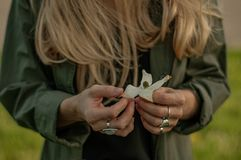 Beautiful woman with long hair holding flower. Hands with rings stylish boho accessories. No focus royalty free stock image
