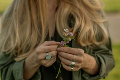 Beautiful woman with long hair holding flower. Hands with rings stylish boho accessories. No focus stock images
