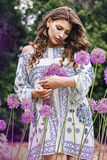 Beautiful woman with long hair among purple flowers Stock Image