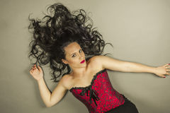 Beautiful woman with long hair and red corset lay down Stock Photo
