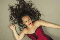 Beautiful woman with long hair and red corset lay down Stock Image