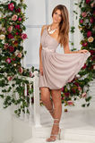 Beautiful woman with long hair standing and posing and in fashion summer dress and trendy shoes with necklace on the neck on brig royalty free stock image