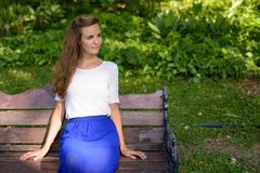 Beautiful woman with long hair thinking while sitting on wooden. Bench in peaceful green park royalty free stock photos