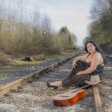 Beautiful woman with long hair and transparent black dress sitting on the train tracks next to a guitar and a hat royalty free stock images