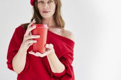 Beautiful woman with long hair wearing red hat and sweater holds paper disposable coffee cup. Space for design template layout. Mock-up royalty free stock image