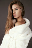 Beautiful  woman with long hair wears luxurious white fur coat Stock Image