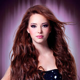 Beautiful woman with long hairs. Beautiful woman with brown long curly hairs over stylized background royalty free stock photo