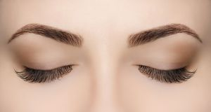 Beautiful Woman with long lashes in a beauty salon. Eyelash extension procedure Stock Photo