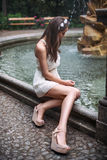 Beautiful woman with long legs sitting near fountain Royalty Free Stock Photos