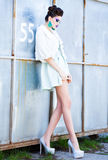 Beautiful woman with long legs in white dress, fur and high-heels posing outdoor Stock Images