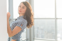 Beautiful woman with long loose hair standing next to wall in spacious light room, posing, looking at camera. Beautiful woman with long loose hair standing next royalty free stock photos