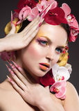 Beautiful woman with long nails, perfect skin, hair of orchids. Royalty Free Stock Image