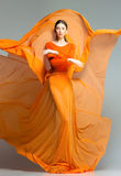 Beautiful woman in long orange dress posing dramatic Royalty Free Stock Images