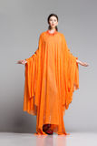 Beautiful woman in long orange dress posing dramatic in the studio Stock Images