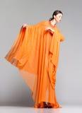 Beautiful woman in long orange dress posing dramatic in the studio Royalty Free Stock Photo