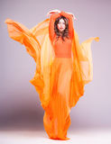Beautiful woman in long orange dress posing dramatic in the studio stock photos