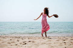 Beautiful woman with long pink dress jumping on a tropical beach Stock Images