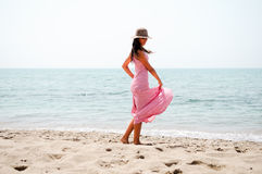 Beautiful woman with long pink dress and sun hat on a tropical b Royalty Free Stock Image