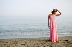 Beautiful woman with long pink dress on a tropical beach royalty free stock photography