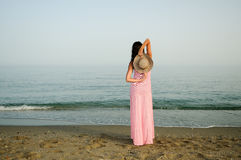 Beautiful woman with long pink dress on a tropical beach Stock Image