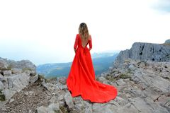 Woman in long red dress on the edge of a cliff in the mountains. Peak of Ai-Petri mountain. Beautiful woman in long red dress staying on the edge of a cliff in Royalty Free Stock Photography