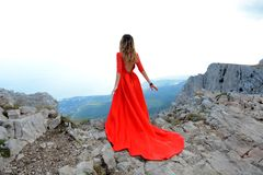 Woman in long red dress on the edge of a cliff in the mountains. Peak of Ai-Petri mountain. Beautiful woman in long red dress staying on the edge of a cliff in Stock Image