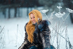 Beautiful woman with long red hair on a snowy Cow Parsnip Stock Photo