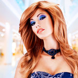 Beautiful woman with long red hairs with blue makeup Stock Photography