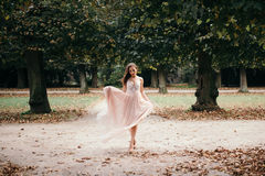 Beautiful woman in long rose evening dress walking path in park. royalty free stock photos
