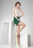 Beautiful woman with long legs dressed elegant posing in the studio - full body Stock Image