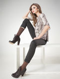 Beautiful woman with long sexy legs in pants and boots posing in the studio Royalty Free Stock Photography