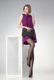 Beautiful woman with long legs in polka dot stockings dressed elegant posing stock photography