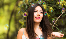 Beautiful woman with long shiny thick hair playing with bubbles Stock Photography