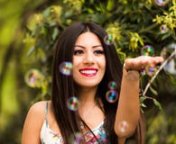 Beautiful woman with long shiny thick hair playing with bubbles Royalty Free Stock Photo
