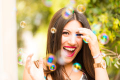 Beautiful woman with long shiny thick hair playing with bubbles Stock Photos