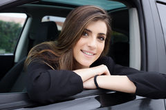Beautiful woman with long silky hair sitting in car smiling Royalty Free Stock Images