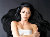 Beautiful  woman with long straight hair. Portrait of a beautiful woman with long straight black hair lying on the dark background Stock Images