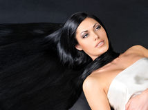 Beautiful  woman with long straight hair. Portrait of a beautiful woman with long straight black hair lying on the dark background Royalty Free Stock Images