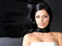Beautiful  woman with long straight hair. Portrait of a beautiful woman with long straight black hair lying on the dark background Royalty Free Stock Photos