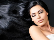 Beautiful  woman with long straight hair. Portrait of a beautiful woman with long straight black hair lying on the dark background Stock Photos