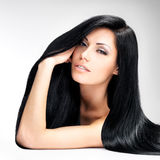 Beautiful woman with long straight hair. Portrait of a beautiful brunette woman with long straight hair poses at grey background stock photos