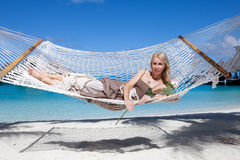Beautiful woman in a long sundress in a hammock on a sea background Royalty Free Stock Photography