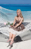Beautiful woman in a long sundress in a hammock on a sea background Royalty Free Stock Images