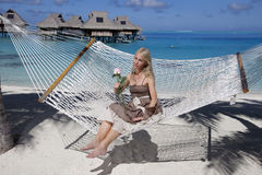 Beautiful woman in a long sundress in a hammock on a sea background Royalty Free Stock Photo