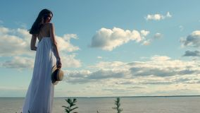 Beautiful woman in long white dress, holding hat in hand, on  background of  sea. Beautiful slender girl in long white dress holds straw hat in her hand, shakes stock video footage