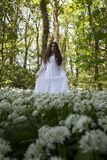 Beautiful woman in long white dress standing in a forest Royalty Free Stock Images