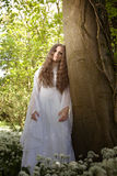 Beautiful woman in long white dress standing in a forest Stock Image