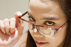 Beautiful woman look through her eyeglasses, concept of finding Royalty Free Stock Images